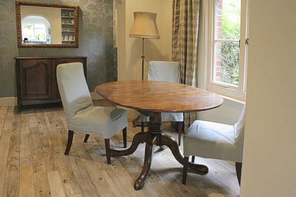 Our Wilmington bespoke range extending oak pedestal dining table, in the dining room of our clients downland village house, in East Sussex.