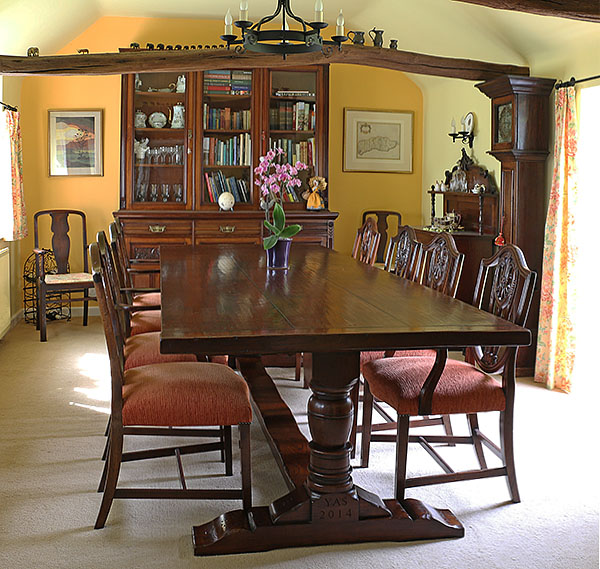 Period style oak pedestal table personalised to our client and pictured in the converted forge of their Sussex cottage.
