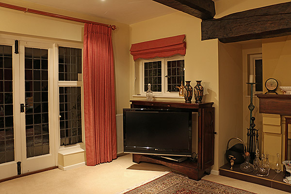Gothic style oak TV cabinet, shown here with the bi-fold doors open, in the sitting room of our clients Surrey home.