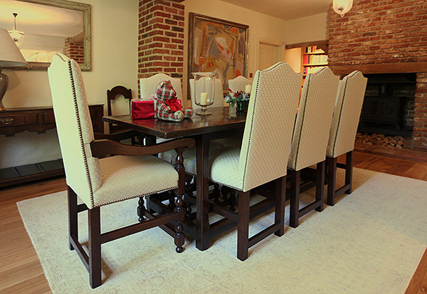 Period style oak upholstered chairs, with our clients 17th century table, in the dining room of their Surrey country home.