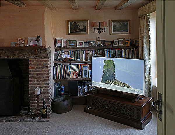 Elizabethan strapwork carved and pierced oak TV stand and custom designed flat screen mount, in an oak beamed cottage interior.