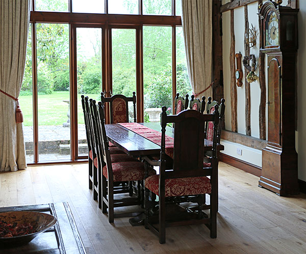 230cm long oak pedestal dining table and period style upholstered oak side chairs and armchairs, pictured here in our clients converted barn, in Kent.