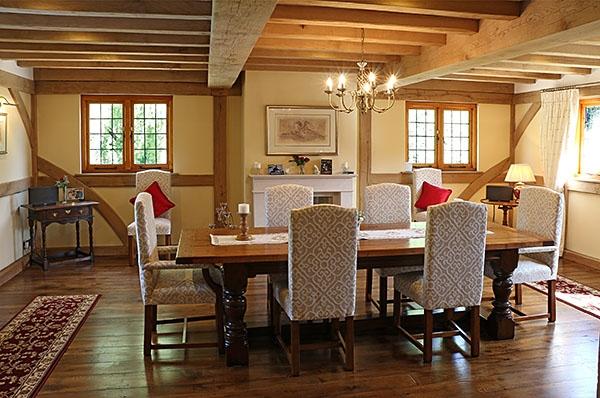 Heavy oak table & upholstered chairs in oak framed room