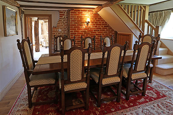 Antique style oak pedestal dining table and upholstered oak dining chairs, in the dining room of our clients old country cottage, in Kent.