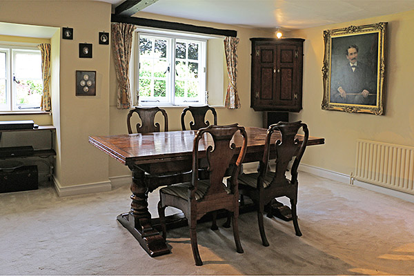 Period style extendable oak pedestal table, shown here in the dining room of our clients West Sussex village cottage.