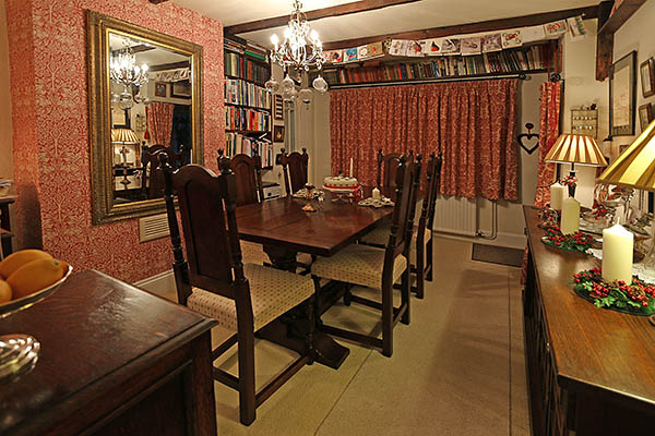 Period style dining table and upholstered chairs in oak beamed Sussex cottage.