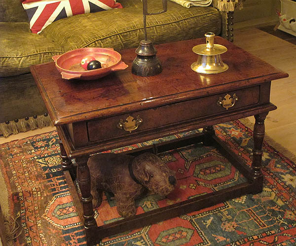 Oak coffee table with drawer, in period interior.