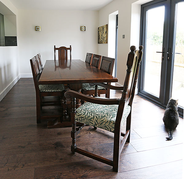 Bespoke and semi-bespoke traditionally styled oak dining room furniture in newly built modern interior.