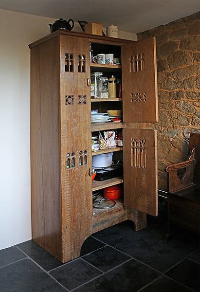 Early 16th century style boarded aumbry, used as kitchen storage cupboard, in Surrey cottage.