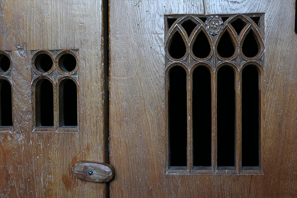 Carved tracery ventilation apertures, on our early 16th century style boarded oak aumbry.