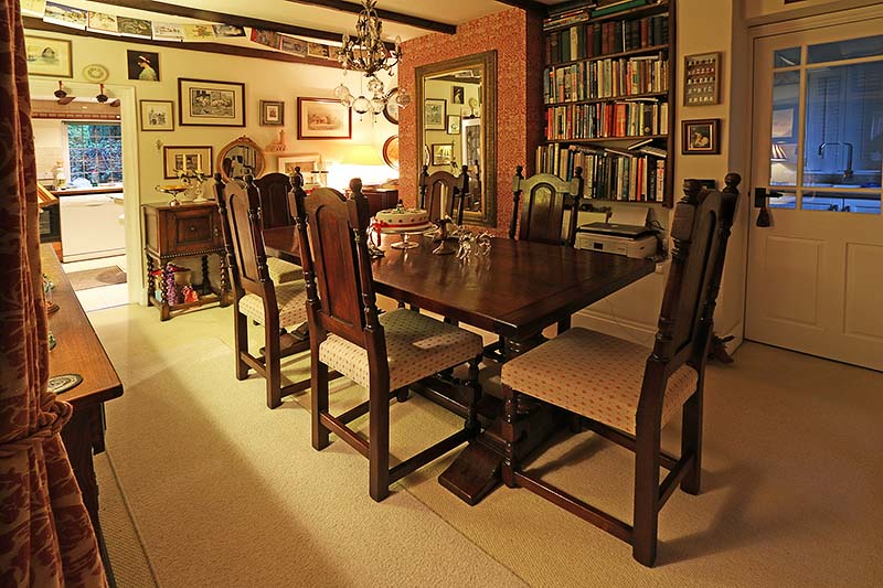 Period style pedestal table and upholstered chairs, in dining room of cottage.