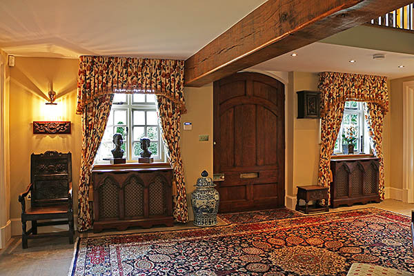Gothic style 3-panel oak radiator covers, in hallway of Warwickshire country home.