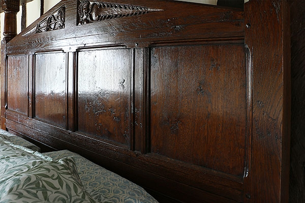 Close-up of carved oak headboard on Tudor Style Bed