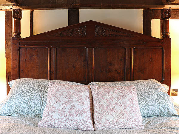 Carved oak headboard and posts, on our clients bespoke Tudor style bed.