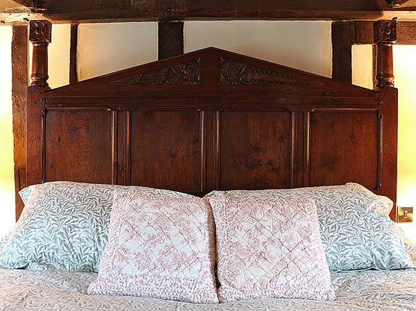 Hand carved oak headboard & posts on Tudor style bed