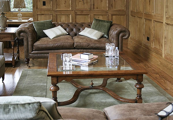Large square glass top coffee table in oak panelled room