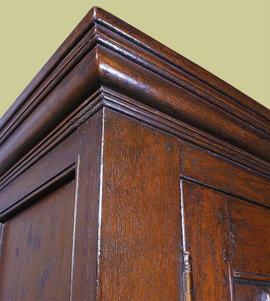 Cornice detail of 16th century style oak linenfold wardrobe.