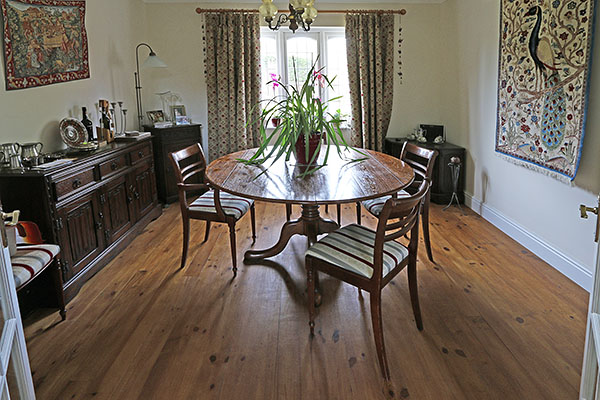 Round oak extending pedestal table, in dining room of West Sussex home.