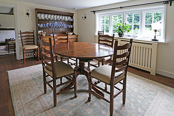 Oak pedestal table and ladderback chairs in Sussex framhouse.