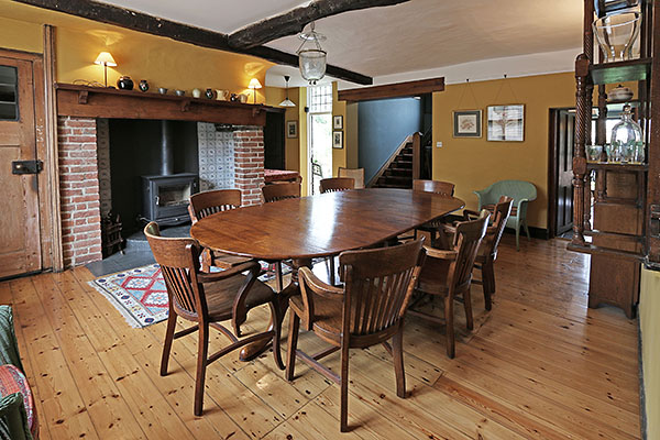 Extending twin pedestal oak table, in dining room of converted period pub.