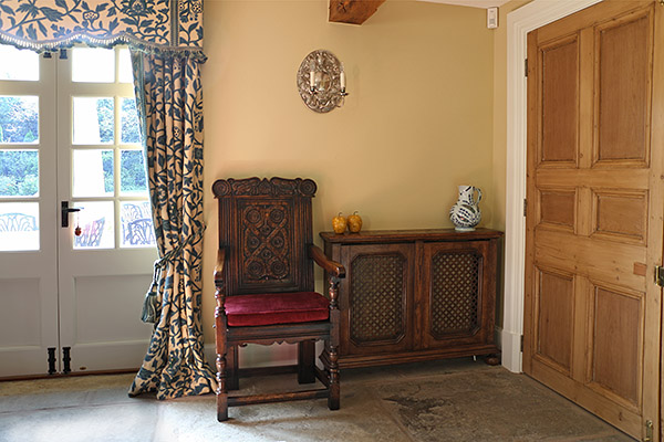 17th century style carved oak armchair and 18th century style oak radiator cover, in Warwickshire country house.