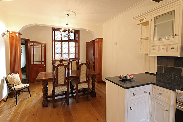 Oak refectory table and upholstered chairs in historic manor house.