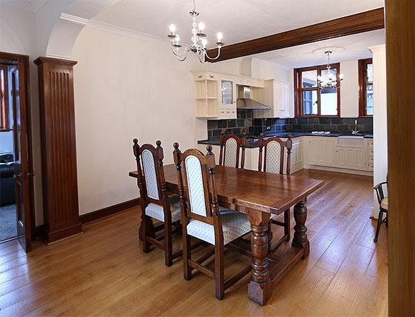 Oak refectory table and upholstered chairs in kitchen of period manor house.