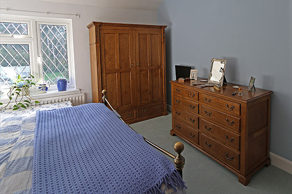 Period style bespoke oak wardrobe and chest of drawers, in master bedroom of clients Surrey country home.