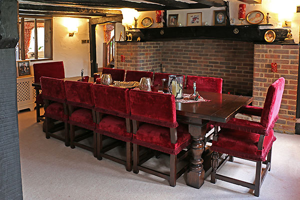 Antique style oak table and upholstered chairs in mid 17th century Surrey home.