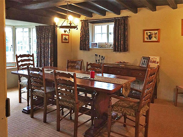 Restored antique table and chairs with oak potboard dresser base, in old manor house.