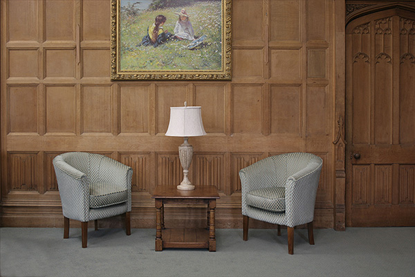 Square lamp table with doric column turned legs, in oak panelled room.