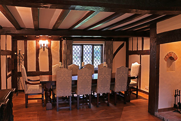 Period style oak table and chairs in timber framed room of 17th century country house.
