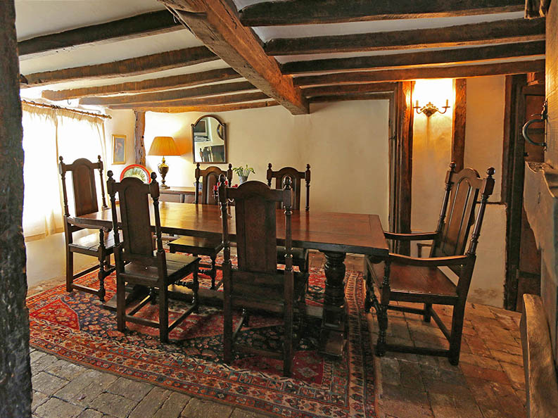 Period style oak pedestal dining table and chairs in ancient beamed room