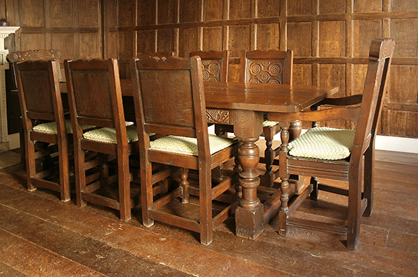 Hand carved period style refectory table and chairs in oak panelled room