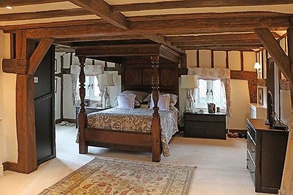 17th century style carved oak tester bed in Surrey cottage