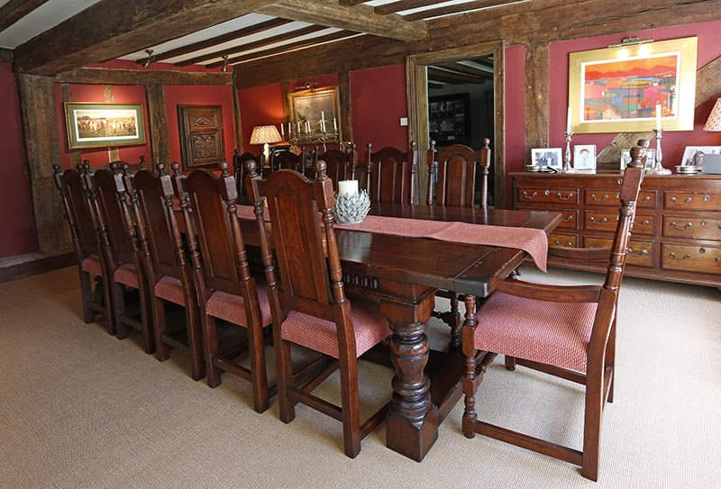 Period style oak table chairs in 16th century timber framed interior