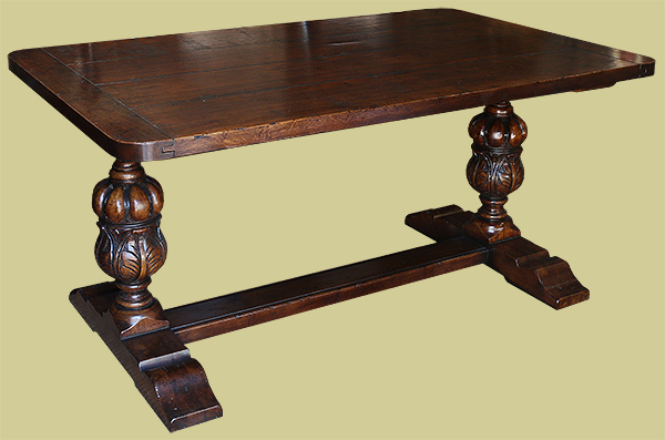 Oak pedestal dining table with Elizabethan style hand carved columns.